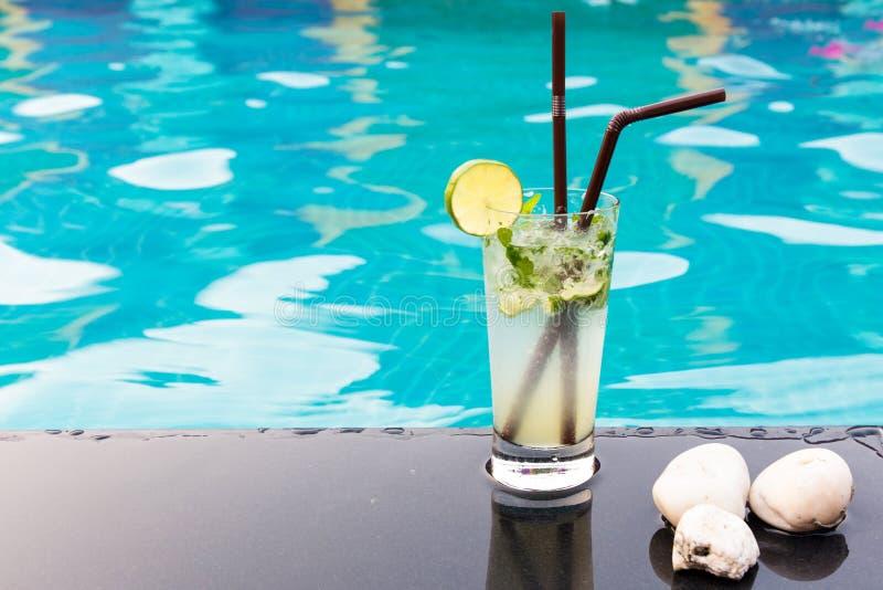 关闭与石灰的鸡尾酒玛格丽塔酒在游泳池附近 免版税图库摄影