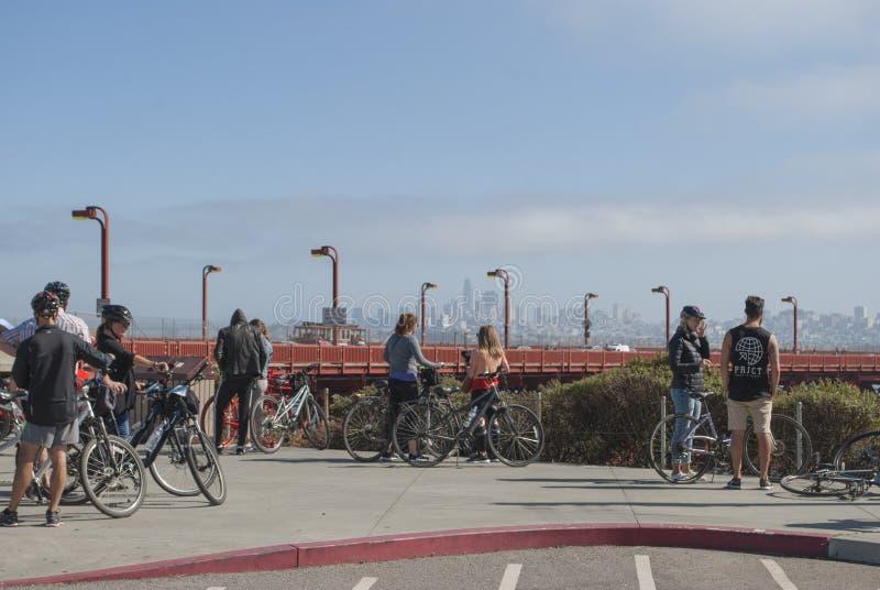 关闭与自行车观看在街市的小组年轻人 人们谈话与背景的摩天大楼 免版税库存照片