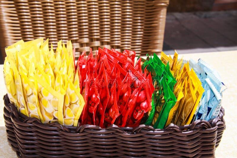 关闭与调味汁小五颜六色的塑料包裹选择的木篮子在室外餐馆的桌上的  免版税库存图片