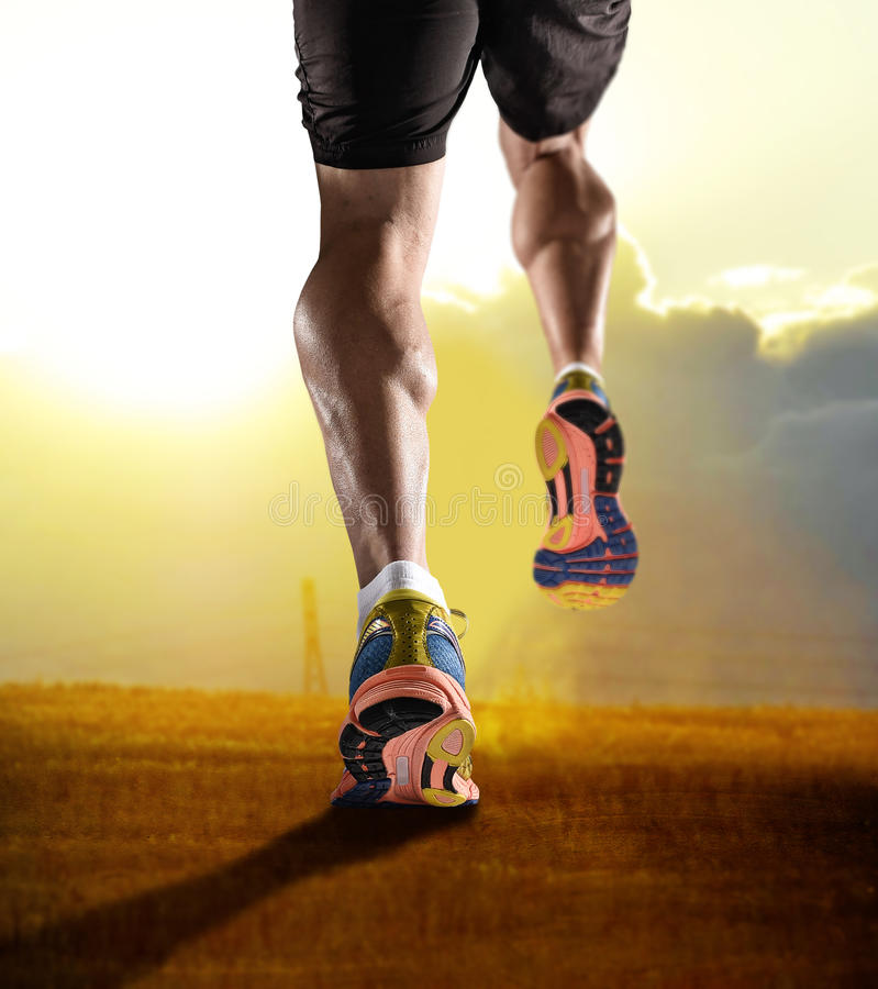关闭与跑步在健身训练日落锻炼的体育人的跑鞋和强的运动腿的脚 库存照片