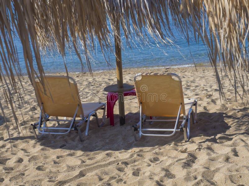 关闭与阳伞的两黄色空的sunbeds在与绿松石明白蓝色海水的希腊沙滩 免版税库存图片
