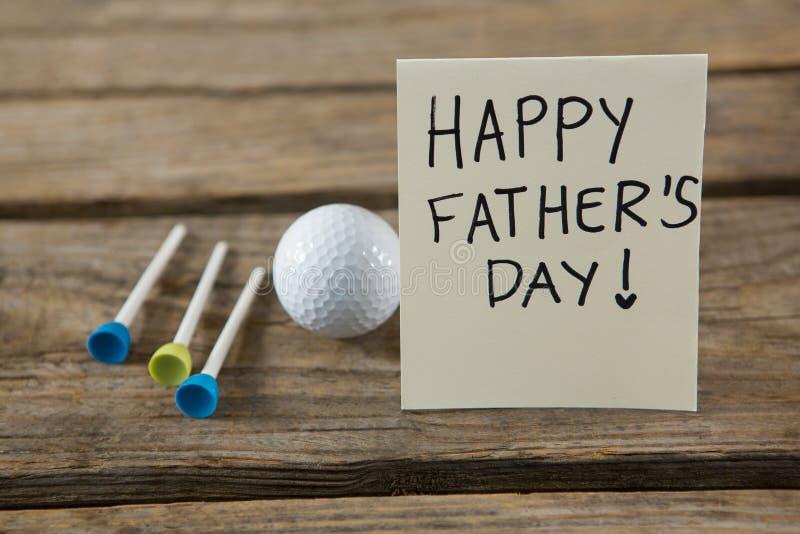 关闭与高尔夫球和发球区域的父亲节消息 库存照片