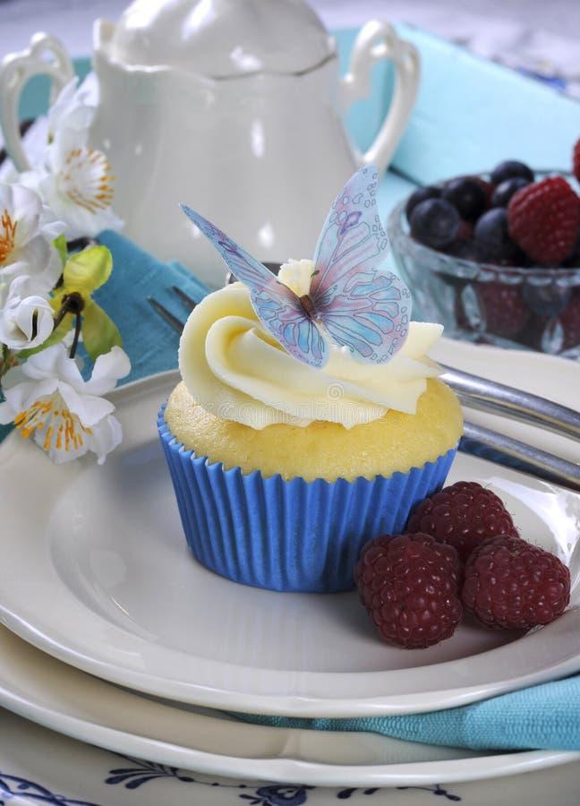 关闭与蝴蝶薄酥饼装饰的可口杯形蛋糕在葡萄酒水色蓝色盘子设置-垂直 免版税图库摄影