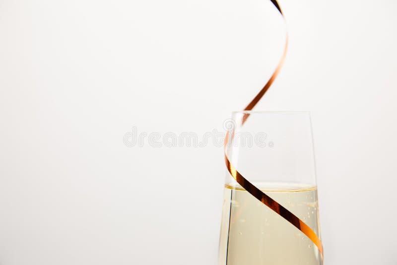 关闭丝带包裹的香槟玻璃射击隔绝在白色背景,假日概念 免版税库存图片