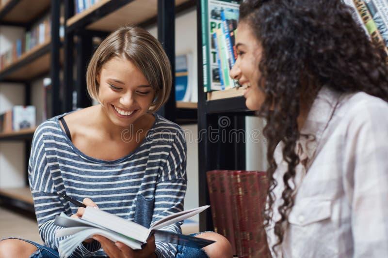 关闭两个快乐的年轻女学生坐地板在图书馆里在研究以后,嘲笑大学故事 免版税图库摄影