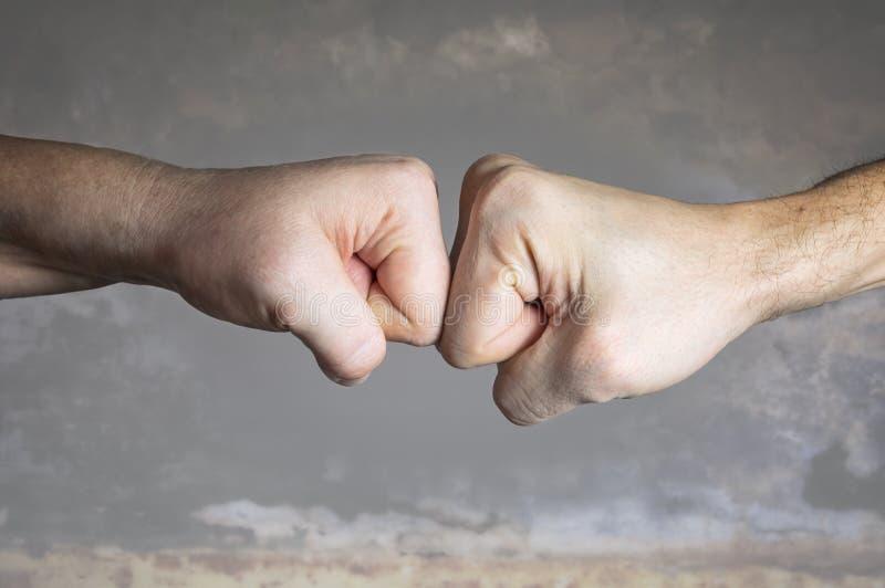 关闭两个拳头碰撞在剧烈的背景的 免版税库存图片