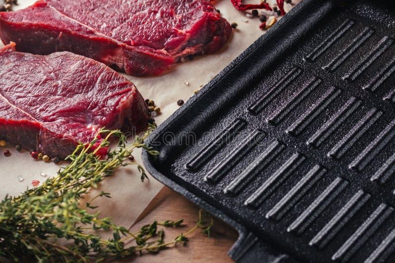 关闭两个新未加工的牛肉肉牛排切片用香料 免版税图库摄影