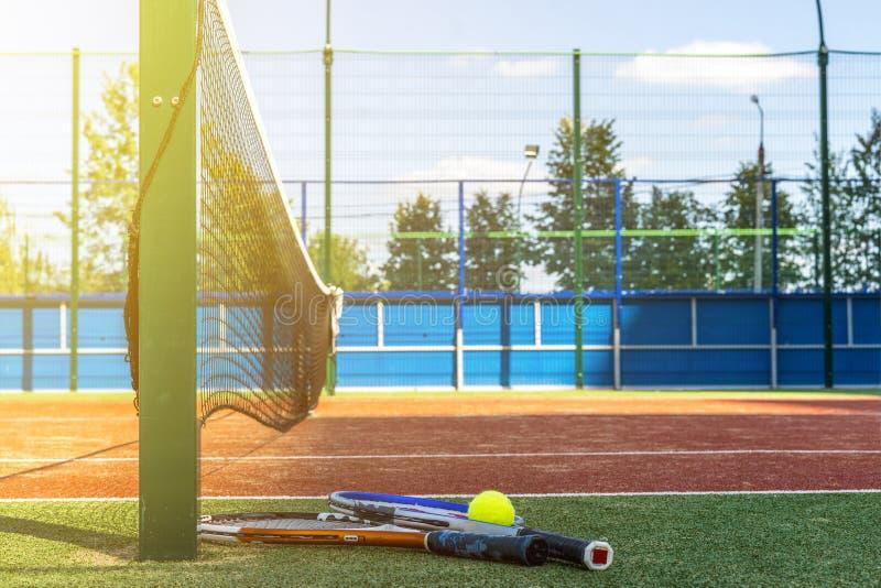 关闭两个网球拍和一个球在地面近的网在网球场 库存照片