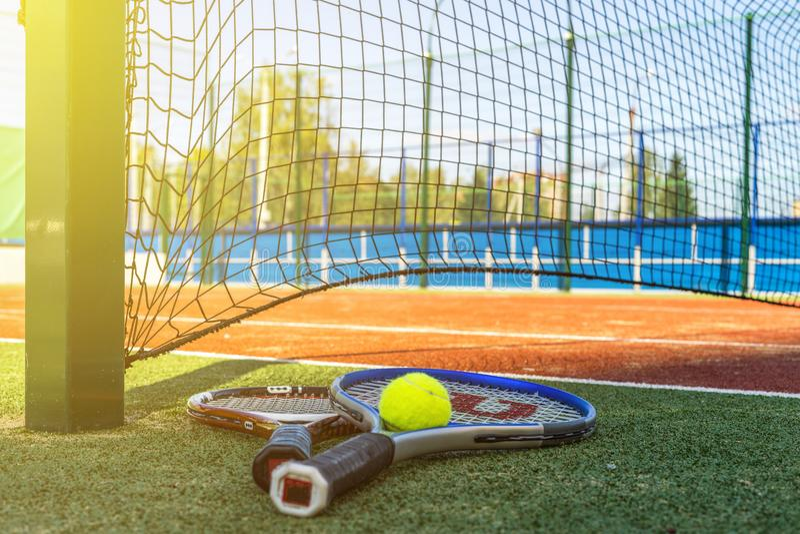 关闭两个网球拍和一个球在地面近的网在网球场 库存图片
