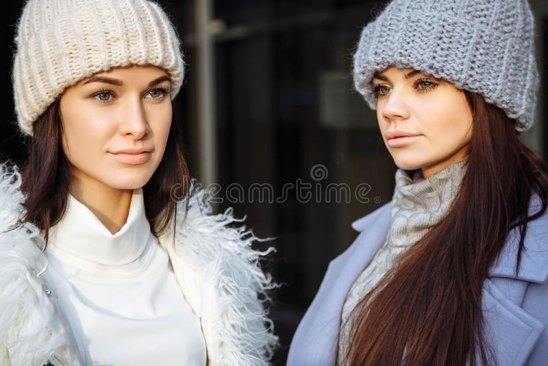 关闭两个美丽的朋友少妇在秋天,佩带摆在灰色背景的冬天衣裳画象  免版税图库摄影