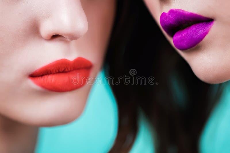关闭两名妇女的红色和紫色嘴唇 库存图片