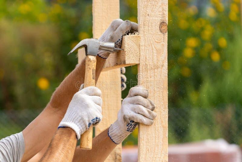 关闭两名工作者播种的照片拿着板条板的白色防护手套的安装它在特别房子拥有 库存照片
