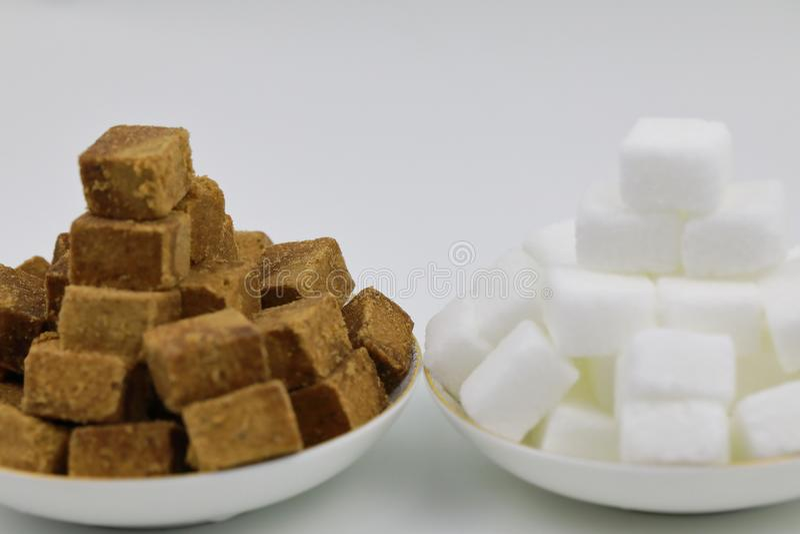 关闭两堆在一块白色板材的红糖立方体在白色背景 库存照片