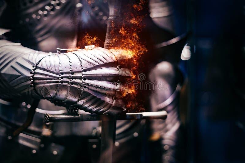 关闭中世纪钢装甲用铁破裂与火火焰的手套手  免版税库存图片