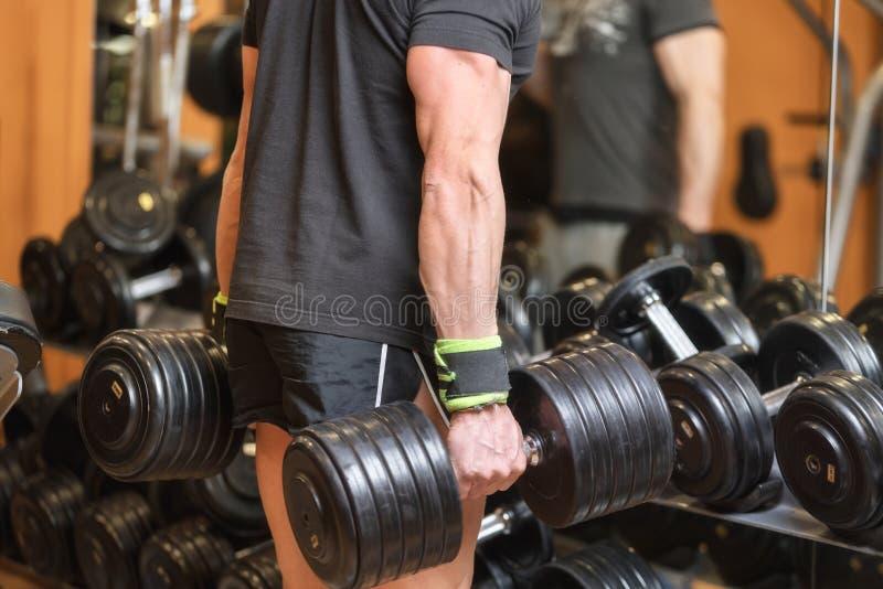 关闭举行在健身房的肌肉人重的哑铃 免版税库存照片