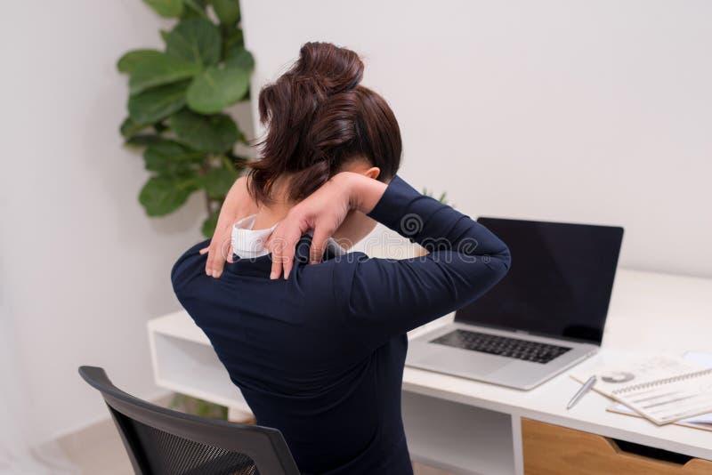 关闭举行她的项机智的一名疲乏的女实业家的背面图 库存图片