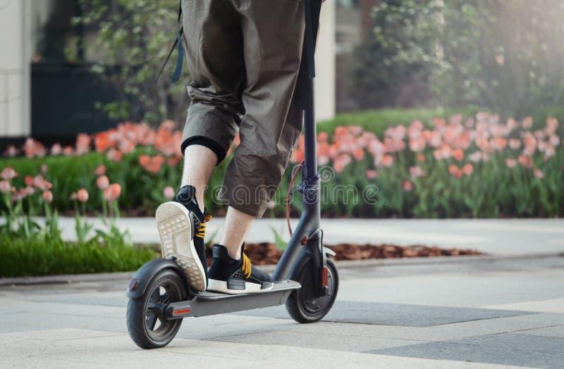 关闭乘坐黑电反撞力滑行车的人在美好的公园风景 库存照片