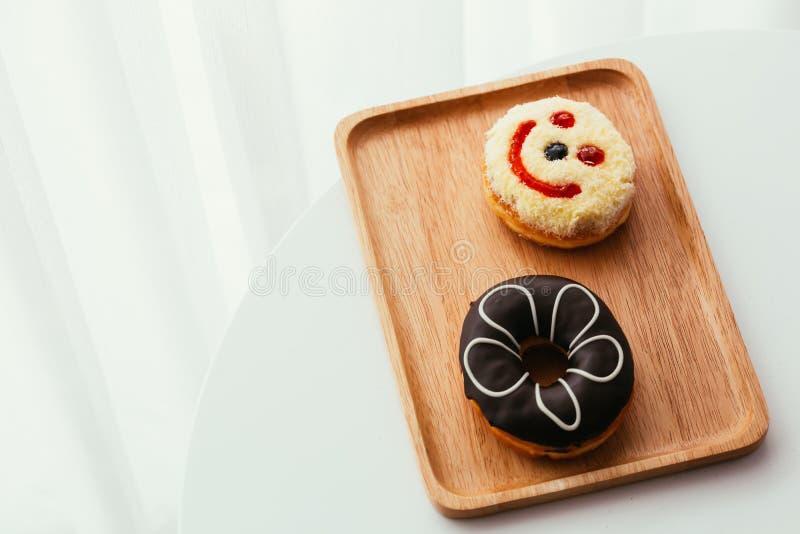 关闭五颜六色和甜油炸圈饼和一个兴高采烈的面孔多福饼在窗口附近 免版税库存图片
