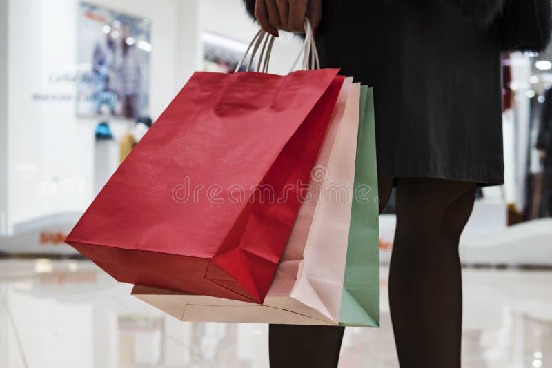 关闭五颜六色的纸袋在购物中心背景的妇女的手上 站立在购物中心的裙子和黑贴身衬衣的妇女 免版税库存图片
