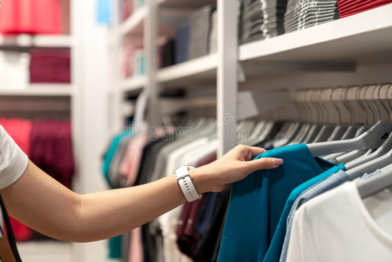 关闭亚洲妇女手购物或选择在机架的偶然蓝色T恤杉在年轻服装店在百货店 图库摄影