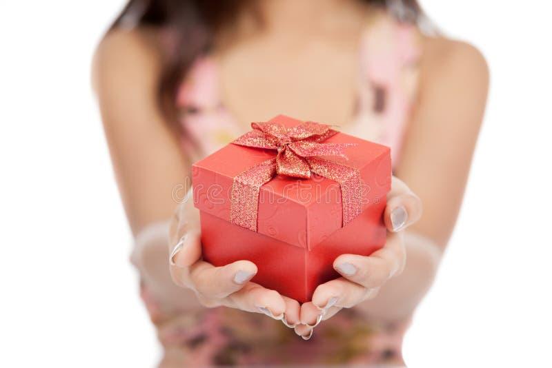 关闭亚裔妇女放弃在礼物的红色礼物盒焦点 图库摄影