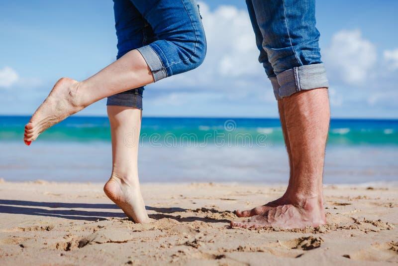 关闭亲吻在海滩的夫妇脚 免版税库存图片