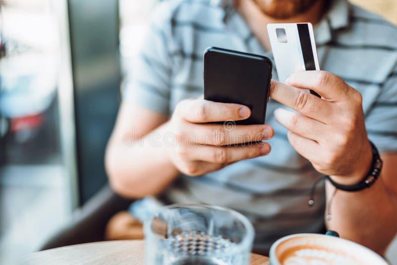 关闭人使用智能手机和网络购物的信用卡细节  免版税库存图片