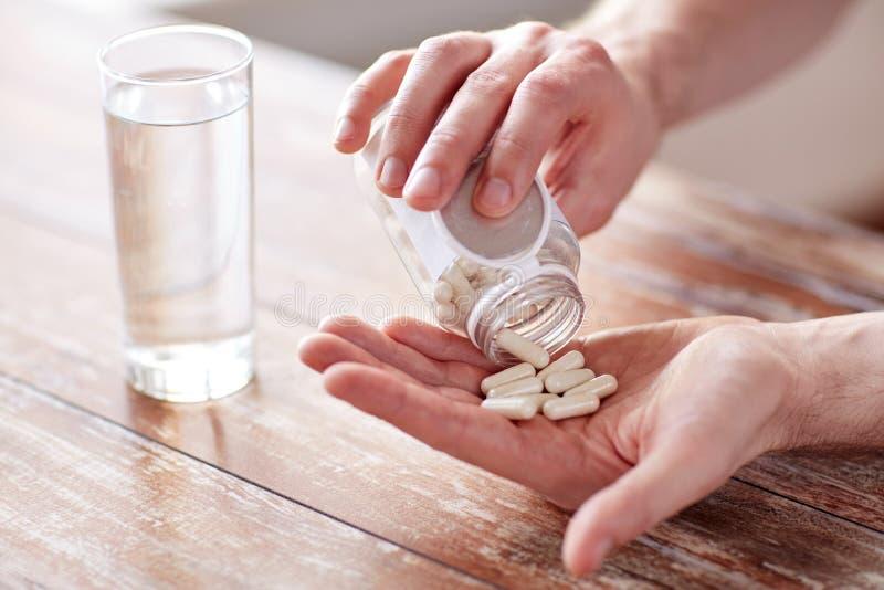 关闭人倾吐的药片从瓶子到手 图库摄影