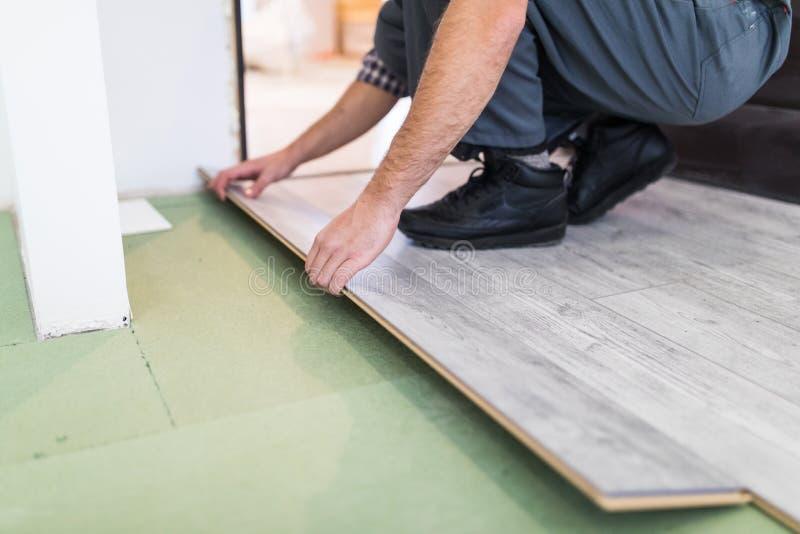 关闭人手安装层压制品的地板的木匠工作者在新的屋子 免版税库存照片