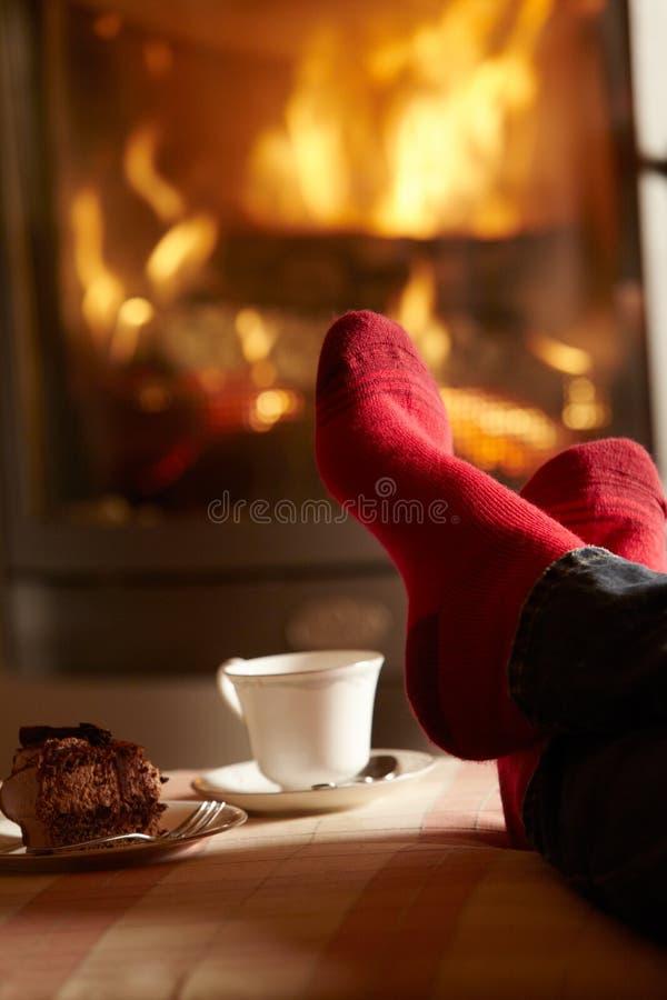 关闭人放松由舒适钻木取火的英尺 免版税库存照片