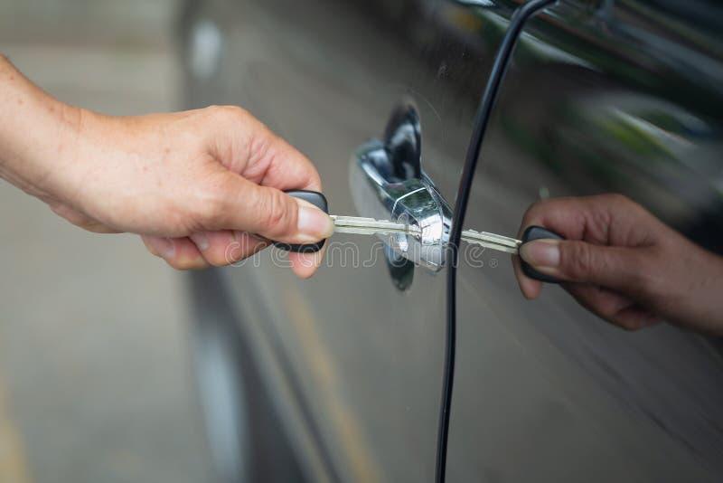关闭人的男性手开头车门,由钥匙打开门汽车 免版税库存图片