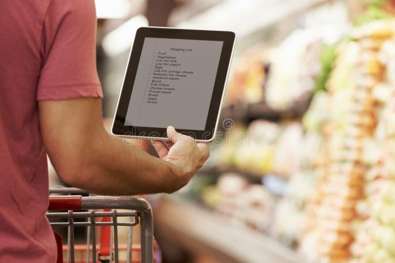 关闭人读书从数字式片剂的购物单在超级市场 免版税库存照片