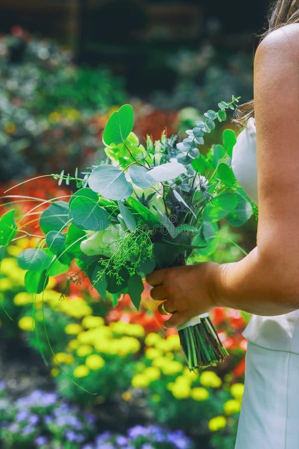 关闭今后看白色的礼服的美丽的妇女新娘,举行婚礼花束在他的手上 免版税库存照片