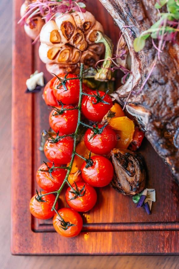 关闭从印第安战斧牛排的烤蕃茄用土豆泥、被烘烤的菠菜乳酪和小汤调味汁 服务用红葡萄酒 库存照片