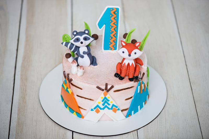 关闭从点心师的蛋糕为生日1岁婴孩 儿童的蛋糕用动物图,圆锥形小屋装饰和 图库摄影