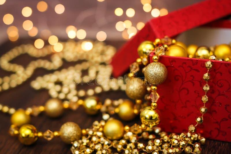 关闭从红色礼物盒的金黄圣诞节装饰球在黑暗的木背景和bokeh诗歌选 图库摄影