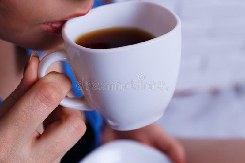 关闭从美好的白色杯子的少妇饮用的咖啡 coz 免版税库存图片