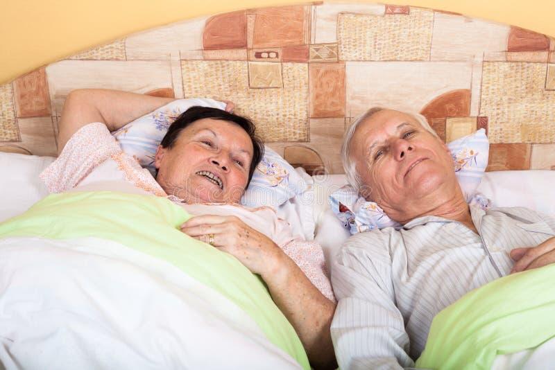 愉快的资深夫妇在床上 免版税库存图片