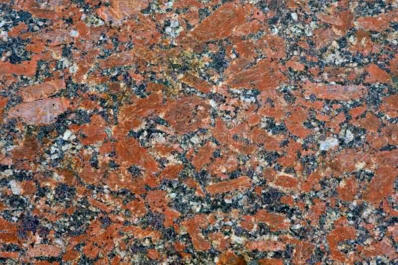关闭优美的红色使有大理石花纹的花岗岩纹理 免版税库存照片