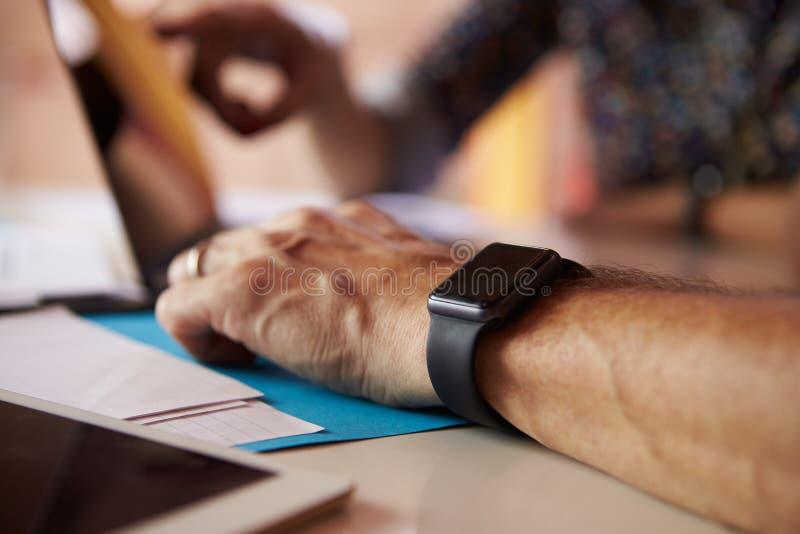 关闭佩带巧妙的手表的商人在设计事务所 免版税库存图片