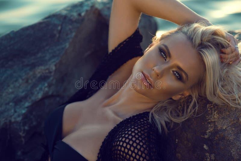 关闭佩带黑泳装和夏天长袍的华美的魅力被晒黑的白肤金发的妇女画象放松在石头在海 图库摄影