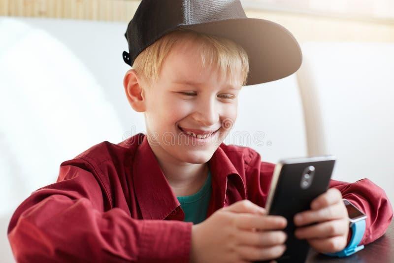 关闭佩带黑他的手机的愉快的微笑的男孩盖帽和红色衬衣冲浪的互联网看有快乐的s的屏幕 免版税库存照片