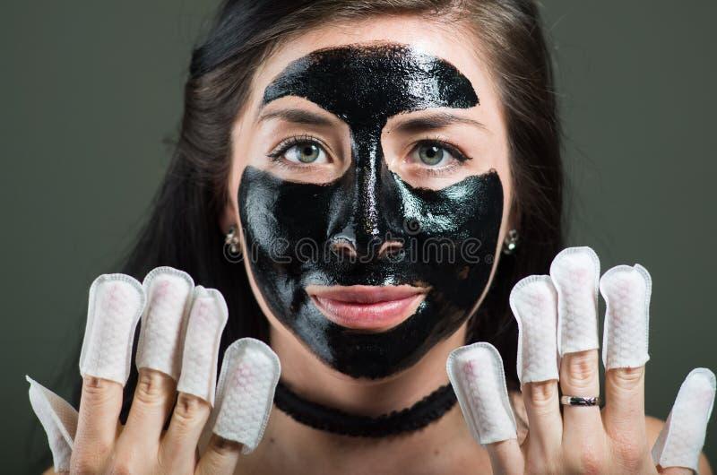 关闭使用一个黑体字面具的秀丽少妇和佩带钉子保护者在她的钉子,在黑背景 免版税库存照片