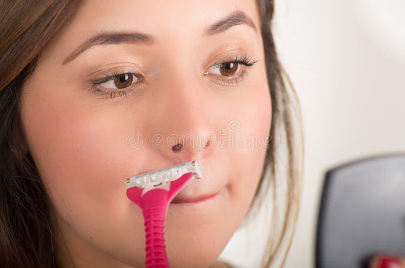 关闭使用剃具的一个美丽的少妇假装刮她的看小镜子,在浴的髭 免版税库存图片