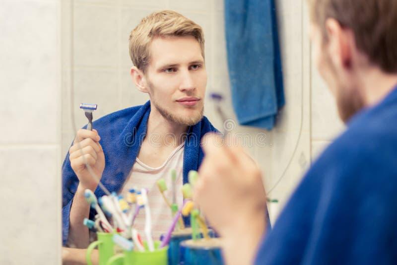 关闭使用剃刀的年轻有胡子的人刮胡子在浴的早晨 库存照片