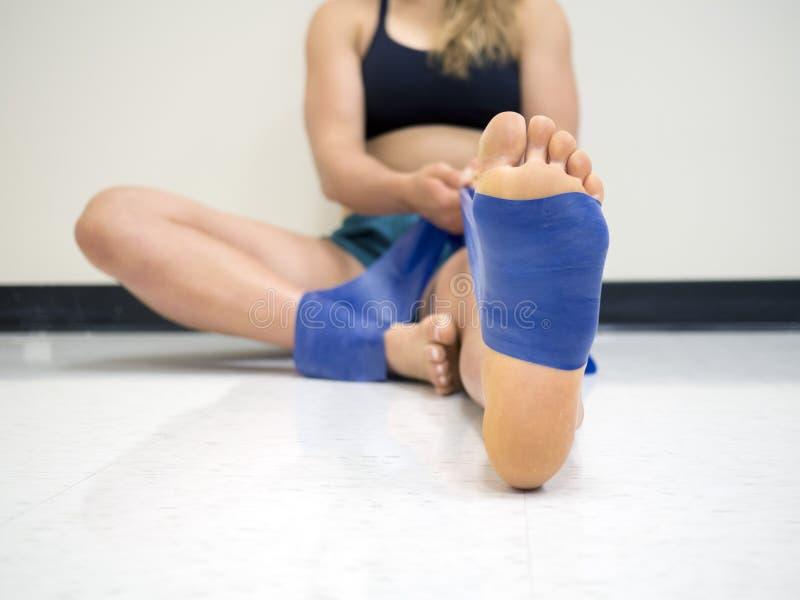 关闭使用在她的脚和脚腕的一个年轻女运动员的底视图一条theraband抵抗带 免版税图库摄影