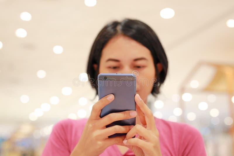 关闭使用在桌上的亚裔妇女智能手机在百货店 免版税库存图片