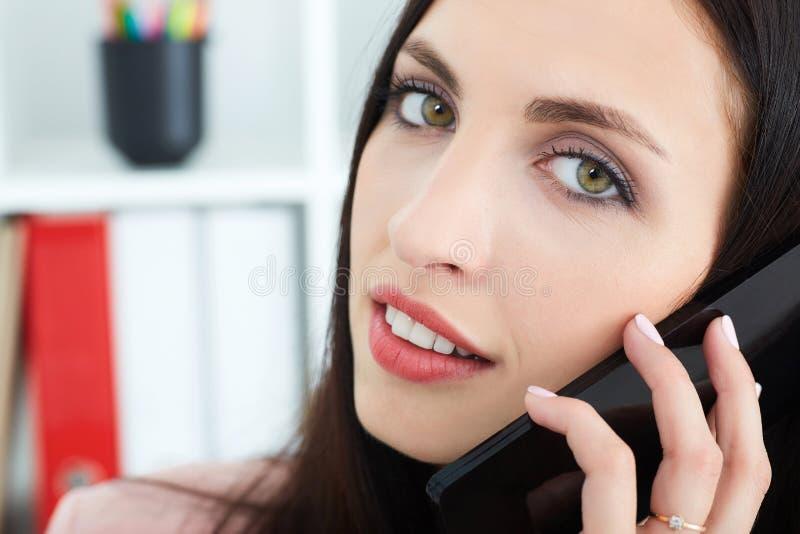 关闭使用手机的一个美丽的女孩的画象在办公室背景 库存照片