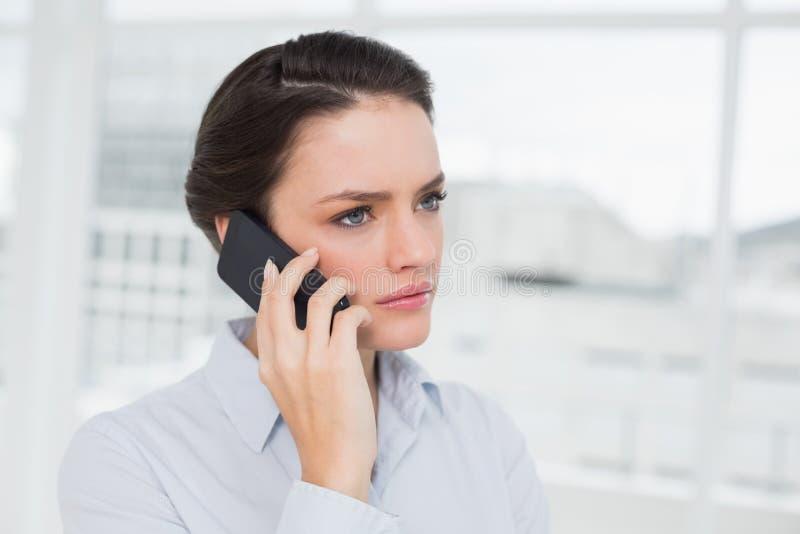 关闭使用手机的一名严肃的典雅的女实业家 免版税库存图片