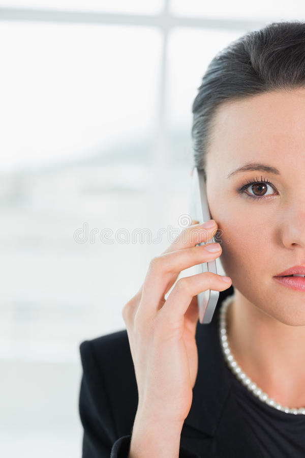 关闭使用手机的一名严肃的典雅的女实业家 免版税库存照片